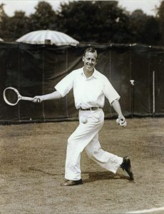 Image of Wilmer Allison about to return a ball on the tennis court. He wears a white shirt and light colored pants. One arm is extended holding a racket. He is mid-motion stepping forward with the upper half of his body turned toward the camera.