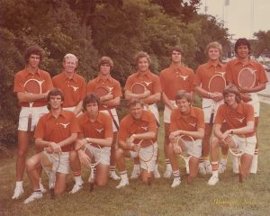 Dave Snyder with the other eleven members of the Longhorn tennis team in their burnt orange tops and white shorts. Snyder is on his left knee and is the third person from the left in the front row.