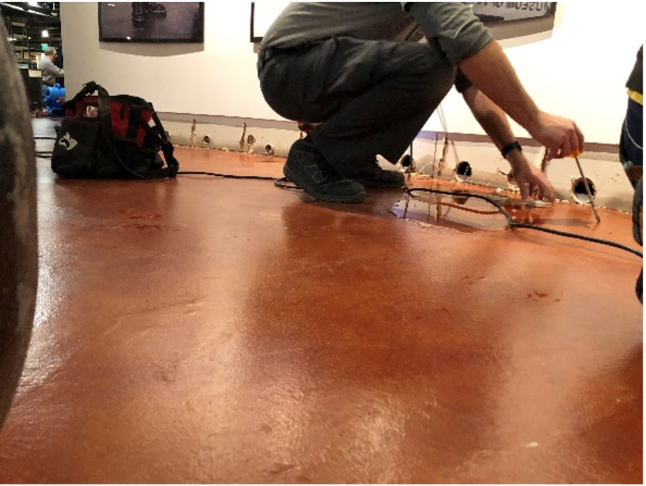 Drilling holes in lobby after removing baseboards.